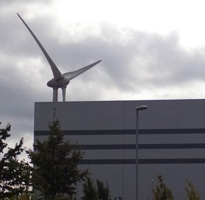 Large Wind Turbine Behind Industrial Building
