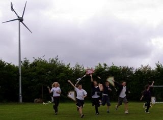 Children Play Near a Wind Turbine at a School